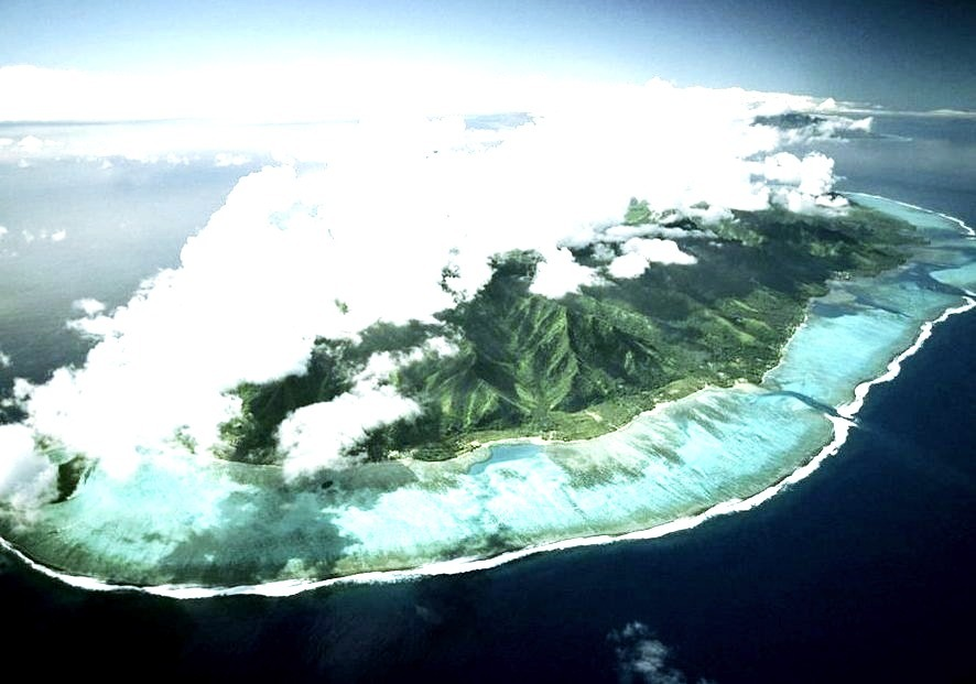 A mass of fluffy white clouds crowns the lush hills of the island of Tahiti